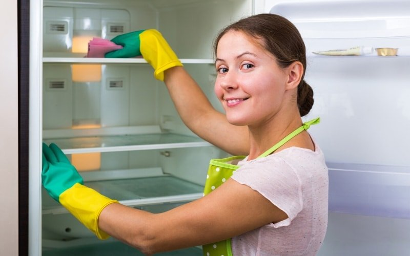 photo of person cleaning a fridge in anticipation of a virtual happy hour activity
