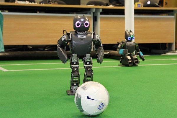 Small humanoid robots kicking a soccer ball